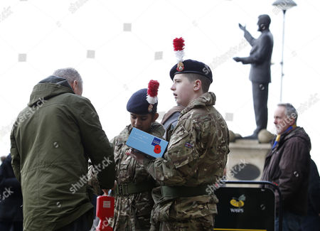 A fan buys a poppy from Army cadets near the Jimmy Hill statue