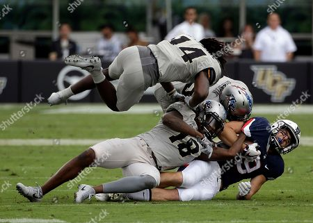 Tyler Davis, Nevelle Clarke, Shaquem Griffin, Kyle Gibson. Connecticut wide receiver Tyler Davis, right, is tackled after a reception by Central Florida defensive back Nevelle Clarke (14), linebacker Shaquem Griffin (18) and defensive back Kyle Gibson, center, during the first half of an NCAA college football game, in Orlando, Fla