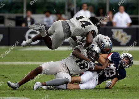Connecticut wide receiver Tyler Davis, right, is tackled after a reception by Central Florida defensive back Nevelle Clarke (14), linebacker Shaquem Griffin (18) and defensive back Kyle Gibson, center, during the first half of an NCAA college football game, in Orlando, Fla