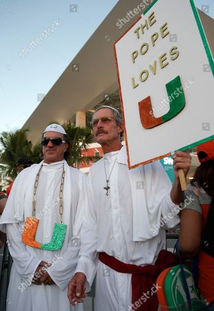 Steve Johnston, Joe Vitale. Miami football fans Steve Johnston, left, and Joe Vitale, of Miami, right, stand outside of Hard Rock Stadium before an NCAA college football game between Miami and Notre Dame, in Miami Gardens, Fla