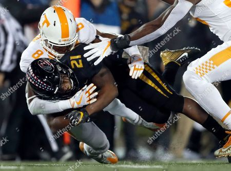Missouri running back Ish Witter (21) is pulled down by Tennessee defensive back Justin Martin (8) during the first half of an NCAA college football game, in Columbia, Mo