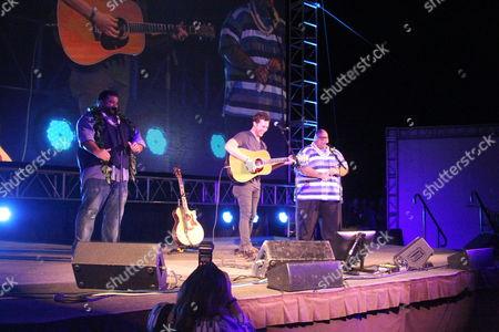 Shawn Mokuahi Garnett and Jorge Garcia join Phillip Phillips onstage at the Sunset on the Beach event for season 8 of the CBS show Hawaii Five-0 on Waikiki Beach in Honolulu, Hawaii - Michael Sullivan/CSM