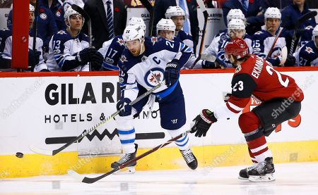 Stock Image of Winnipeg Jets right wing Blake Wheeler (26) passes the puck in front of Arizona Coyotes defenseman Oliver Ekman-Larsson (23) during the first period of an NHL hockey game, in Glendale, Ariz. The Jets defeated the Coyotes 4-1