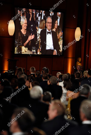 Owen Roizman, Mona Lindholm. Cinematographer Owen Roizman, a recipient of an honorary Oscar, and his wife Mona Lindholm appear on a video screen as he receives a standing ovation at the 2017 Governors Awards at The Ray Dolby Ballroom, in Los Angeles
