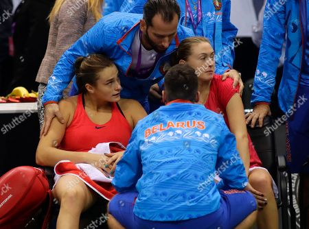 Belarus' Aliaksandra Sasnovich, right, and her teammate Aryna Sabalenka, left, are comforted by teammates after loosing the Fed Cup final match against United States' CoCo Vandeweghe and Shelby Rogers, in Minsk, Belarus, Sunday, Nov.12, 2017. United States defeated Belarus 3-2 and gained the Fed Cup title