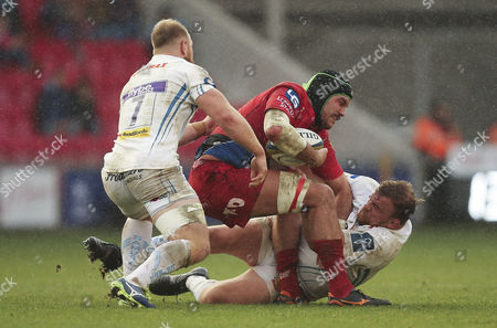 Tom Price of Scarlets is held by Moray Low of Exeter Chiefs and Matt Kvesic of Exeter Chiefs