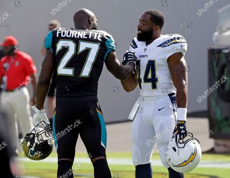 Jacksonville Jaguars running back Leonard Fournette (27) greets Los Angeles Chargers running back Andre Williams (44) before the first half of an NFL football game, in Jacksonville, Fla