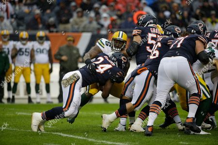 Mike Daniels, Jordan Howard. Green Bay Packers' Mike Daniels (76) tackles Chicago Bears' Jordan Howard (24) during the first half of an NFL football game, in Chicago