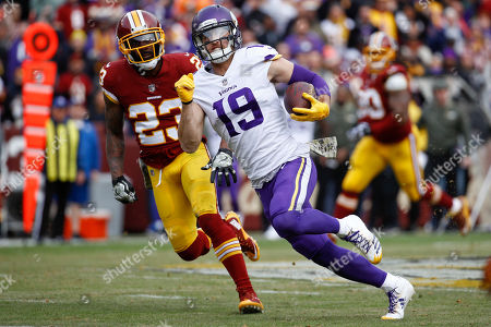 Minnesota Vikings wide receiver Adam Thielen (19) carries the ball past Washington Redskins free safety DeAngelo Hall (23) during the first half of an NFL football game in Landover, Md