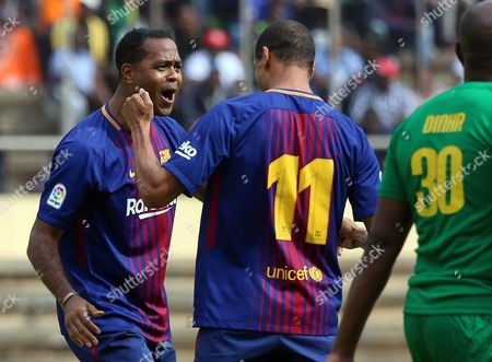 Barcelona FC legend Patrick Kluivert (L) reacts with Rivaldo after scoring a goal during an exhibition soccer match played between Zimbabwe legends and the Barcelona legends at the  National Sports Stadium, Harare, Zimbabwe, 12 November 2017. The match was organised to promote Zimbabwe as a safe tourist destination and also to help to establish links between Zimbabwe and Barcelona soccer.