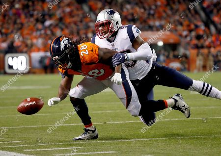 Denver Broncos running back Jamaal Charles (28) can't make the catch as New England Patriots linebacker Marquis Flowers (59) defends during the first half of an NFL football game, in Denver