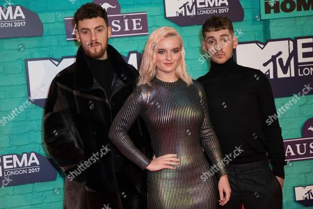 Grace Chatto, center, and brothers Jack and Luke Patterson of music band Clean Bandit pose for photographers upon arrival at the MTV European Music Awards 2017 in London, Sunday, Nov. 12th, 2017