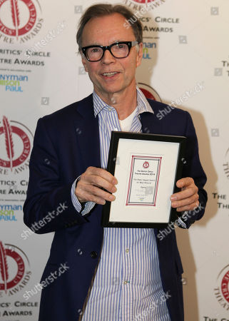 Director Jonathan Kent poses for photographers after winning the award for best musical at the Critics' Circle Theatre Awards in central London on