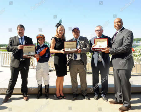 New York Yankees legend Bernie Williams, right, and Sebastien Zbinden, left, and Jennifer Judkins, both of Longines, present watches from the Longines Conquest Classic collection to jockey Javier Castellano, trainer Brian Lynch, second right, and owner representative Bob Feld, center, after their horse Coffee Clique won the $500,000 Longines Just a Game Stakes, at Belmont Park in New York. Longines, the Swiss watchmaker known for its elegant timepieces, is the Official Watch and Timekeeper of the 146th running of the Belmont Stakes