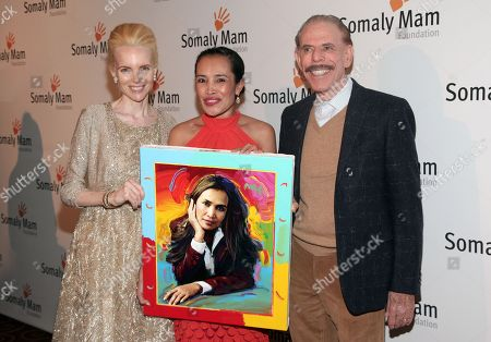 Artist Peter Max, right, with his wife Mary Max, left, present author and human rights advocate Somaly Mam, center, with an original painting at the Somaly Mam Foundation Gala, in New York