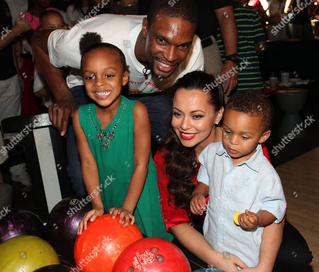 The Miami Heat's Chris Bosh and wife Adrienne Williams Bosh pose with their children during Team Tomorrow Inc. Celebrates Christmas at Santa Bosh's Workshop on at Lucky Strike Lanes in Miami Beach, FL