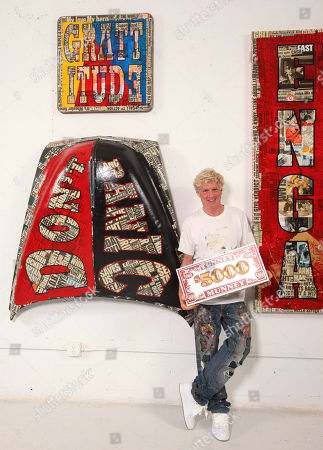 """Artist Peter Tunney, of New York, poses with his art during his """"Lost & Found"""" Art Basel Miami exhibition, at the Peter Tunney Experience inside the Wynwood Walls in Miami"""