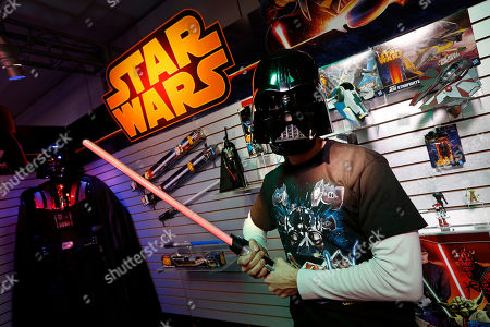 Stock Photo of Toy demonstrator Jeff Wolf gets in touch with his Dark Side wearing the STAR WARS DARTH VADER VOICE CHANGING HELMET and holding the STAR WARS ANAKIN TO DARTH VADER LIGHTSABER in Hasbro's showroom at the American International Toy Fair, in New York