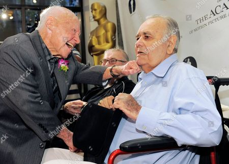 "Mickey Rooney, left, a cast member in the 1963 film ""It's a Mad, Mad, Mad, Mad World,"" greets fellow cast member Jonathan Winters the kick-off of The Last 70mm Film Festival presented by the Academy of Motion Picture Arts and Sciences, at the Samuel Goldwyn Theater in Beverly Hills, Calif"