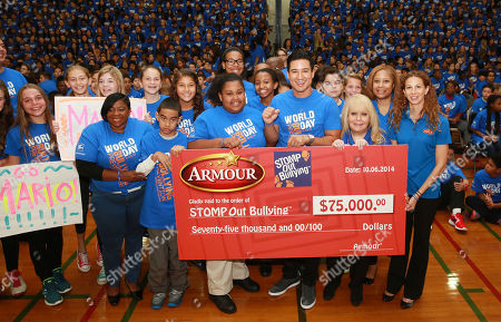 Mario Lopez along with Ross Ellis, STOMP OUT Bullying's founder and CEO, and students of Albert Leonard Middle School hold a check for $75,000 from Armour for Albert Leonard Middle School's anti-bullying efforts at the STOMP OUT Bullying Pep Rally with Mario Lopez, at Albert Leonard High School, on in New Rochelle, N.Y