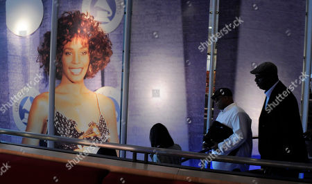 """The late singer Whitney Houston's brother Gary Houston, far right, exits the """"Whitney! Celebrating the Musical Legend of Whitney Houston"""" exhibit at The Grammy Museum, in Los Angeles"""