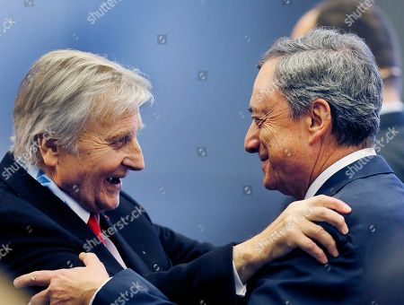 ECB President Marion Draghi, right, and his predecessor Jean-Claude Trichet welcome each other at the Policy Panel of the European Central Bank in Frankfurt, Germany