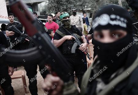 Palestinian armed men attend a military march marking the fifth anniversary of killing Ahmed Jabari, the late leader of the Ezz-Al Din Al Qassam Brigades, the armed wing of Palestinian Hamas movement, near his house in Al Shejaeiya neighborhood, east of Gaza City, 14 November 2017. Ahmed Jabari was killed in an Israeli airstrike on 14 November 2012.