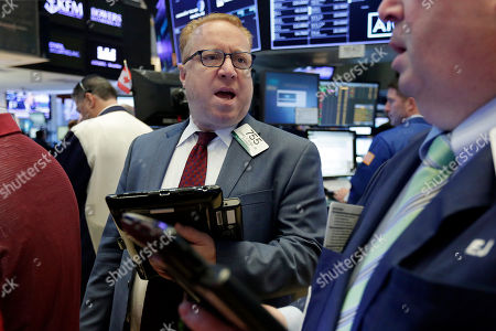 Trader Daniel Ryan, center, works on the floor of the New York Stock Exchange, . Stocks are opening lower on Wall Street as technology companies, banks and retailers sink