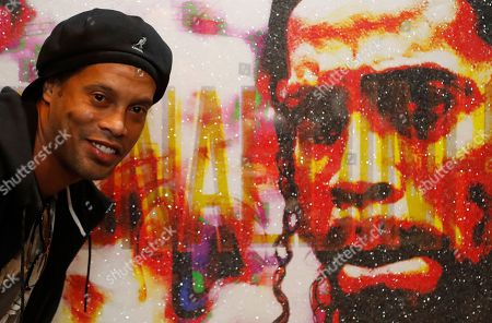 Brazilian soccer player Ronaldinho poses in front of his portrait by Artist Lincoln Townley in London, . The portrait will be auctioned at the inaugural Football for Peace Ball Nov. 17, 2017, at the Guildhall in London. The Ball, hosted by the Vice President of FIFA, HRH Prince Ali Bin Al Hussein of Jordan, will announce the launch of the London City For Peace youth project by Football for Peace