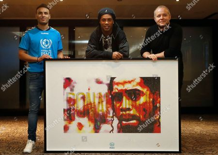 Brazilian soccer player Ronaldinho, center, poses with his portrait by Artist Lincoln Townley, right, and co-founder of Football for Peace, Kashif Siddiqiin, left, in London, . The portrait will be auctioned at the inaugural Football for Peace Ball Nov. 17, 2017, event at the Guildhall in London. The Ball, hosted by the Vice President of FIFA, HRH Prince Ali Bin Al Hussein of Jordan, will announce the launch of the London City For Peace youth project by Football for Peace