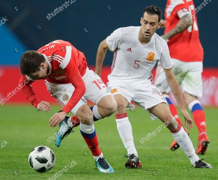 Russia's Daler Kuzyayev, left, struggles for the ball with Spain's Sergio Busquets during the international friendly soccer match between Russia and Spain in St.Petersburg, Russia