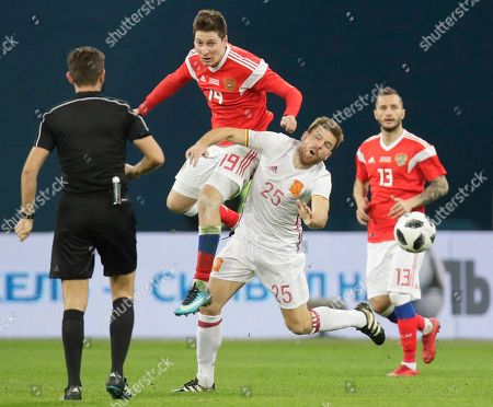 Russia's Daler Kuzyayev, atop, struggles for the ball with Spain's Asier Illarramendi during the international friendly soccer match between Russia and Spain in St.Petersburg, Russia