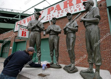"""Trevor Lane, of Boston, places flowers at the foot of a statue of Hall of Fame Boston Red Sox baseball player Bobby Doerr, second statue from left, outside Fenway Park, in Boston. Doerr, who was dubbed the """"silent captain"""" by longtime Red Sox teammate and life-long friend Ted Williams died Monday, Nov. 13, 2017, in Junction City, Ore., the Red Sox said Tuesday in a statement. He was 99. Other statues depict Red Sox players Ted Williams, left, Johnny Pesky, second from right, and Dom DiMaggio, right"""