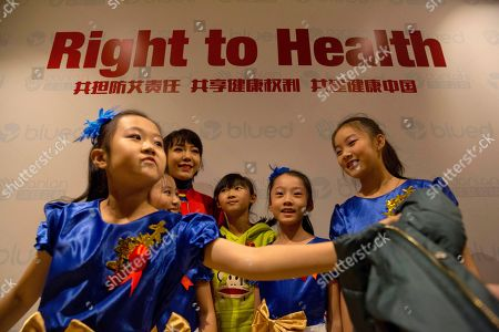 Stock Photo of Chinese singer Wu Mochou, in red, poses for photos with young performers at an event to raise awareness ahead of World AIDS Day in Beijing, China, . The event was hosted by Danlan Public Welfare ahead of the 30th World AIDS Day to promote the use of mobile technology to prevent the spread of HIV in the LGBT community