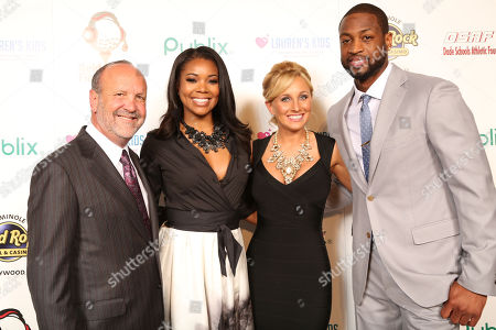 Stock Picture of Ron Book, Chairman of Lauren's Kids, Gabrielle Union, Lauren Book, Founder and CEO of Lauren's Kids and Dwyane Wade, of the Miami Heat, attend the 8th Annual Reid & Fiorentino Call of the Game Dinner Presented by Publix on at the Seminole Hard Rock Hotel & Casino in Hollywood, Fla