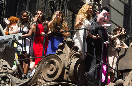 """Fifth Harmony members, from left, Normani Kordei, Lauren Jauregui, Ally Brooke Hernandez, Dinah Jane Hanse and Camila Cabello wave alongside the """"Hotel Transylvania 2"""" costumed characters at the world premiere of their new video """"Hotel Transylvania 2"""" at the Hard Rock Cafe, in New York"""