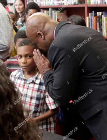 Chess Grand Master Maurice Ashley whispers some advice to a student at a news conference to announce an initiative by Ascension and the St. Louis Chess club to start chess clubs in the schools of the Ferguson-Florissant school district, at Walnut Grove Elementary School in Ferguson, MO