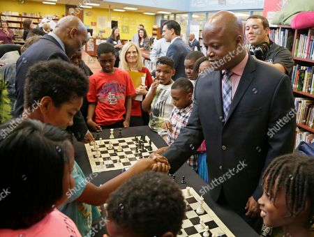 Stock Photo of Chess Grand Master Maurice Ashley, right, shakes the hand of his opponent, a student from Walnut Grove Elementary School, after defeating him in a friendly match at a news conference to announce an initiative by Ascension and the St. Louis Chess club to start chess clubs in the schools of the Ferguson-Florissant school district, at Walnut Grove Elementary School in Ferguson, MO