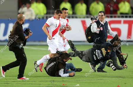 Photojournalists fall as Peru's Christian Cueva (L) and Aldo Corzo (R) celebrate after the FIFA World Cup 2018 qualification playoff second leg match between Peru and New Zealand, at the National Stadium of Lima, Peru, 15 November 2017.
