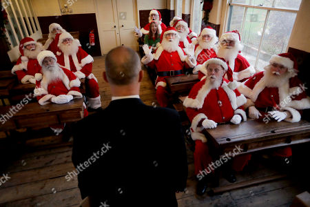 Performers dressed as Santa Claus and one as an elf, take part in a posed classroom photocall for the media for the Ministry of Fun Santa School led by its founder James Lovell, center, at the Ragged School Museum in east London, . The Ministry of Fun Santa School is Britain's only genuine training school for professional Santas, preparing them to help out in grottos, department stores, attractions and events over the Christmas period