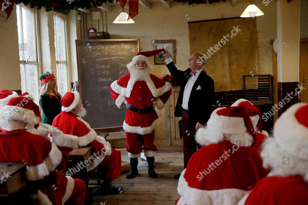 Founder and instructor James Lovell talks through the finer points of outfit details as performers dressed as Santa Claus and an Elf take part in a posed classroom photocall for the media for the Ministry of Fun Santa School at the Ragged School Museum in east London, . The Ministry of Fun Santa School is Britain's only genuine training school for professional Santas, preparing them to help out in grottos, department stores, attractions and events over the Christmas period