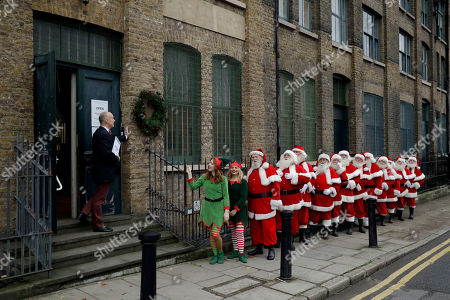 Performers dressed as Santa Claus and Elves stand posed in a line with founder and instructor James Lovell during a photocall for the media for the Ministry of Fun Santa School outside the Ragged School Museum in east London, . The Ministry of Fun Santa School is Britain's only genuine training school for professional Santas, preparing them to help out in grottos, department stores, attractions and events over the Christmas period