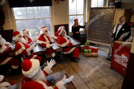 Performers dressed as Santa Claus and Elves take part in a posed classroom photocall for the media for the Ministry of Fun Santa School led by its founder James Lovell at the Ragged School Museum in east London, . The Ministry of Fun Santa School is Britain's only genuine training school for professional Santas, preparing them to help out in grottos, department stores, attractions and events over the Christmas period