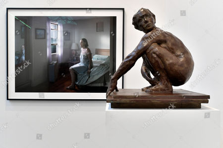 A view of the digital pigment print 'Seated Woman on Bed' (L) by American artist Gregory Crewdson and an untitled bronze statue (Woman Squatting) (R) by American artist Eric Fischl on display in the international art fair ART DUESSELDORF at Areal Boehler, in Duesseldorf, Germany, 16 November 2017. Around 80 established and young galleries from 21 countries will present modern and contemporary art from between 1945 and 2017 in the halls of the former factory complex Areal Boehler. The fair's first edition will be held from 17 to 19 November 2017.