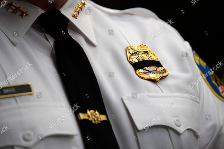 Baltimore Police Department Commissioner Kevin Davis wears a black mourning band across his badge as he speaks at a news conference outside the R Adams Cowley Shock Trauma Center in Baltimore, to announce the death of Det. Sean Suiter. Suiter was shot in the head Wednesday while working in a troubled area of the city grappling with high crime rates