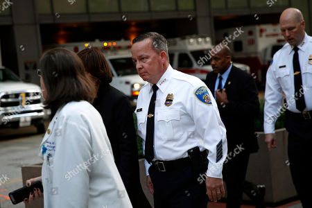 Baltimore Police Department Commissioner Kevin Davis, center, walks past ambulance bays outside the R Adams Cowley Shock Trauma Center in Baltimore, after announcing the death of Det. Sean Suiter. Suiter was shot in the head Wednesday while working in a troubled area of the city grappling with high crime rates