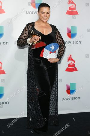 """Olga Tanon poses in the press room with the award for best tropical fusion album for """"Olga Tanon Y Punto"""" at the 18th annual Latin Grammy Awards at the MGM Grand Garden Arena, in Las Vegas"""