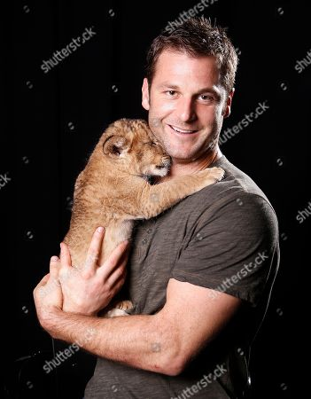 """Stock Photo of Canadian large predator animal expert, television producer and star of ANIMAL PLANET'S """"Frontier Earth"""", Dave Salmoni and his baby lion pose for a portrait, on in New York"""