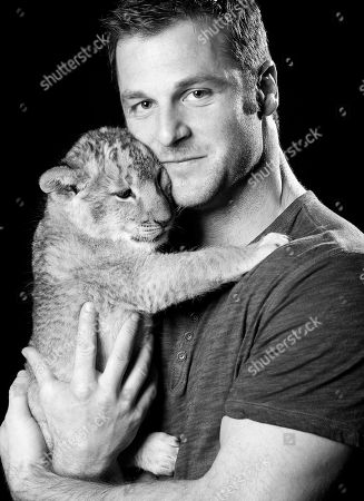"""Stock Image of Canadian large predator animal expert, television producer and star of ANIMAL PLANET'S """"Frontier Earth"""", Dave Salmoni and his baby lion pose for a portrait, on in New York"""