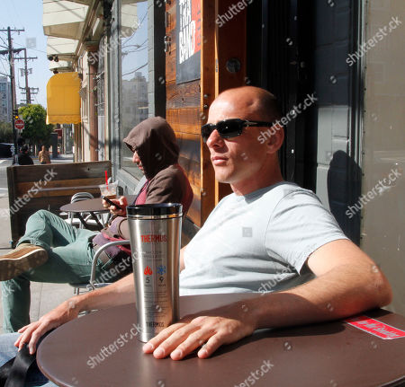 "John Davison sits with his ""free fill"" of coffee on the inaugural ""National Fill Your Thermos Brand Bottle Day,"" at Contraband Coffee Bar in San Francisco. This event is being held in select cities and coffee shops throughout the nation, hosted by the iconic Genuine Thermos Brand, to kick off the holiday weekend"